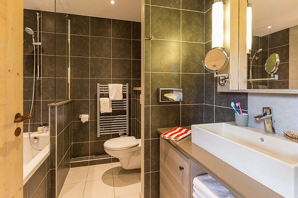 Image of the bathroom in an apartment of Les Terrasses d'Helios including sink, mirror, toilet, bath and towel rail.