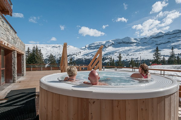 Image of people in the outdoor hot tub at overlooking the piste at Les Terrasses d'Helios
