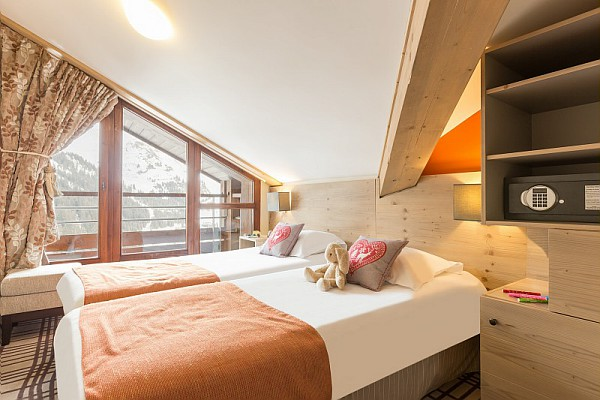 Image of made twin beds in a bedroom with balcony overlooking piste and a safe