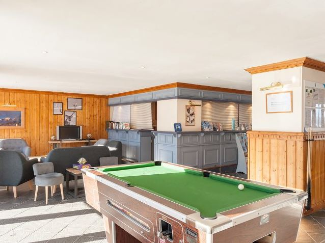 Image of the communal bar area featuring pool table, television and sofas within Residence Le Mont Soleil La Plagne