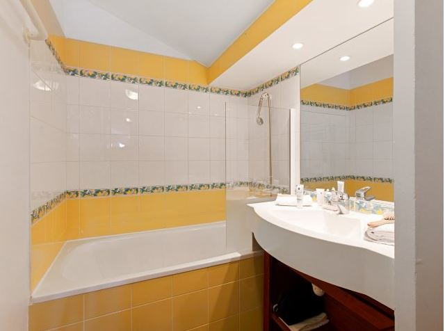 Image of the bathroom in an apartment of Residence Le Mont Soleil La Plagne Soleil, including bath, over bath shower, mirror and sink