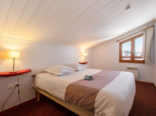 Image of a double bed in a room within an apartment in Residence Le Mont Soleil in La Plagne Soleil