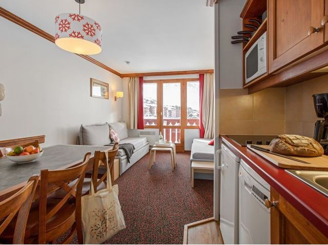 Image of the living area including sofa bed, kitchenette and dining table within Residence Le Mont Soleil La Plagne