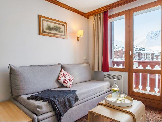 Image of sofabed in the living area overlooking views of the piste at Residence Le Mont Soleil La Plagne Soleil