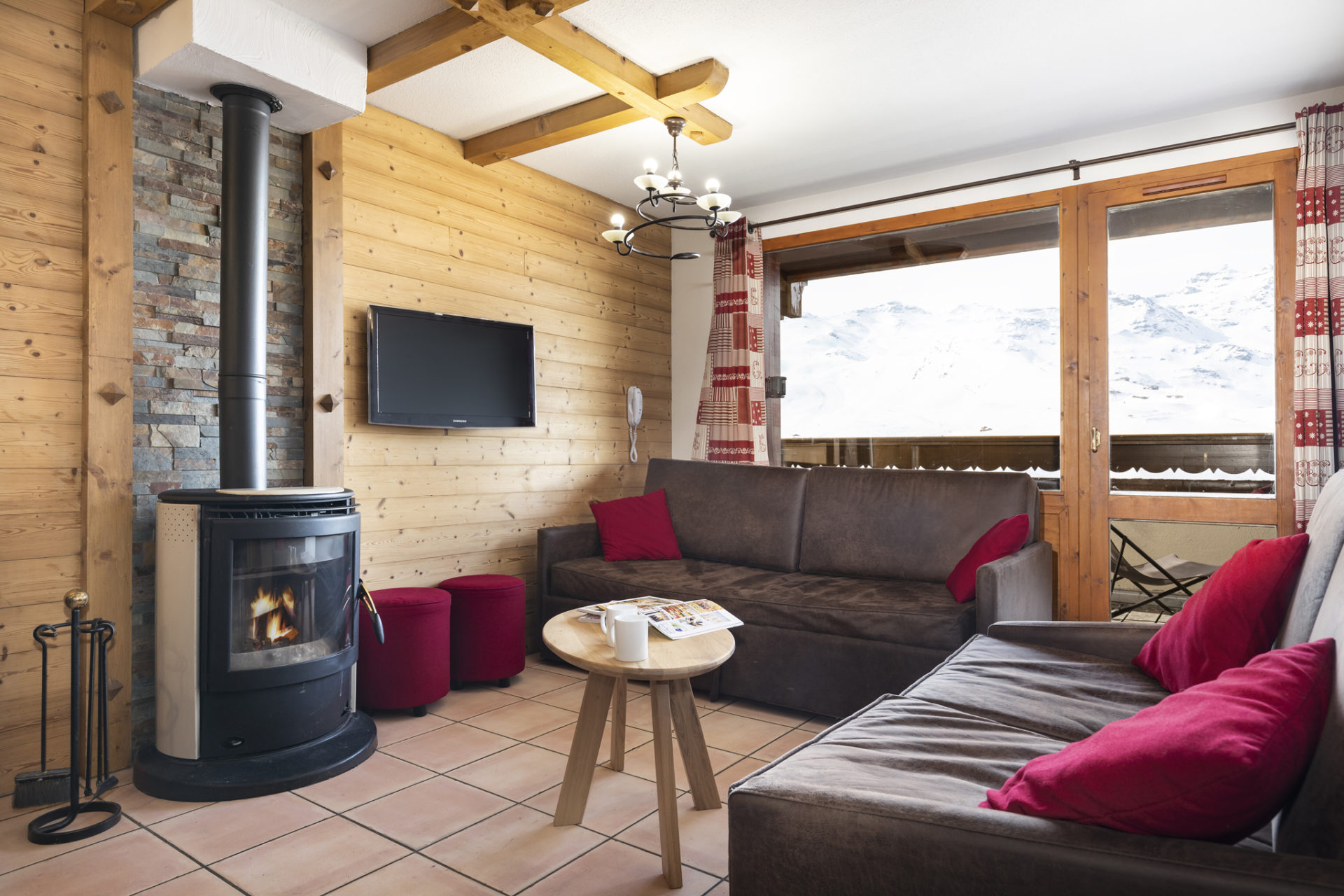 Image of the living area in an apartment in Les Balcons de Val Thorens featuring sofas, TV and a wood burner
