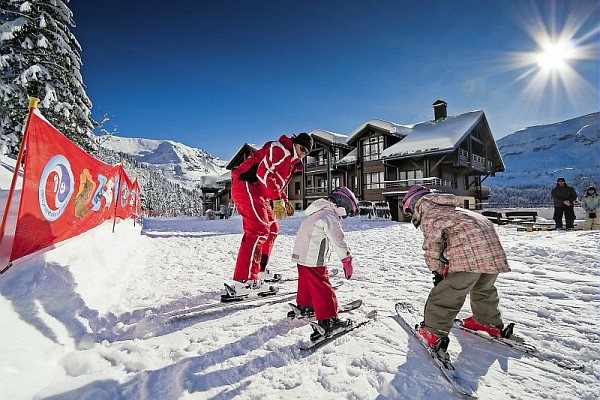 An image of 2 young children at an ESF ski lesson with an instructor