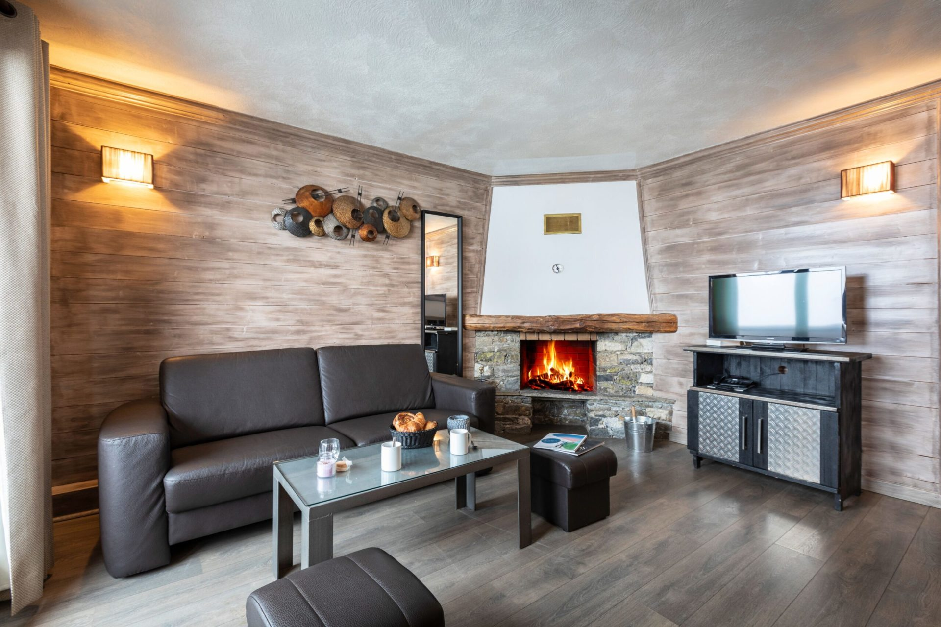 An image of the living area featuring a fire in Chalet des Neiges Residence Hermine