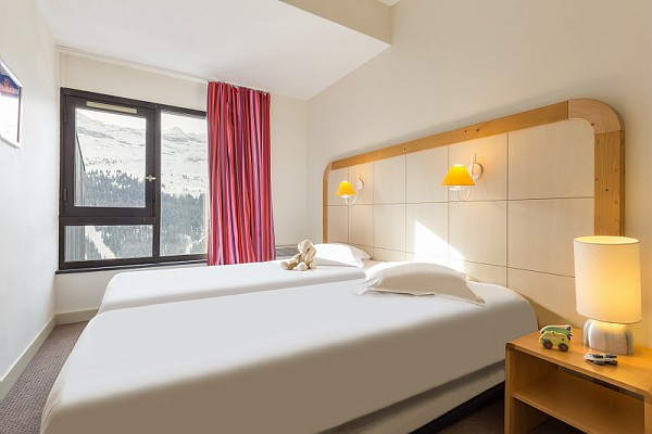 This is a picture of a bedroom in one of the apartments at Residence de la Foret Flaine